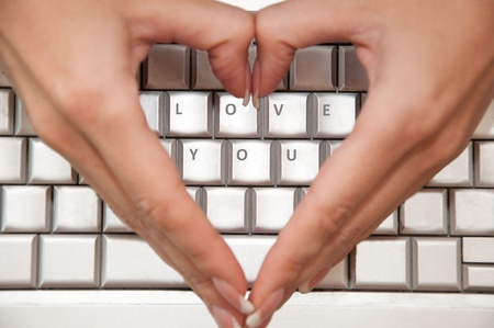 Heart shaped hands over LOVE YOU buttons photo