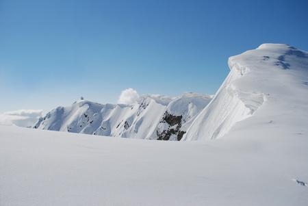 하얀 눈 산 위에 구름 아래 겨울 풍경.