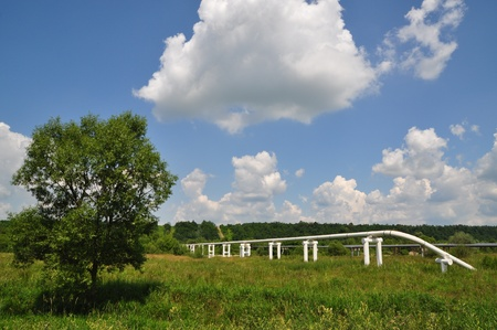 swapping: The main oil pipeline of a high pressure in a summer landscape under clouds.