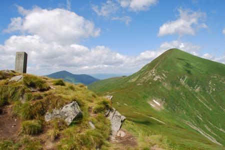 hillsides: Green mountain top in a summer landscape with hillsides under clouds