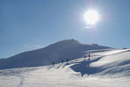A winter mountain landscape with tourists, the sun and far top photo