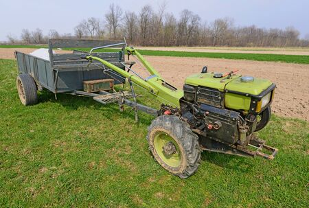 The motor-block with the trailer on a spring field Stock Photo - 19752490