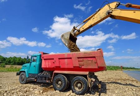 Excavator loads gravel car  photo