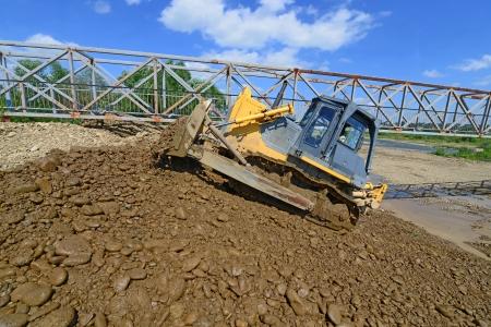 earthwork: Bulldozer at work to strengthen the shoreline of the river  Stock Photo