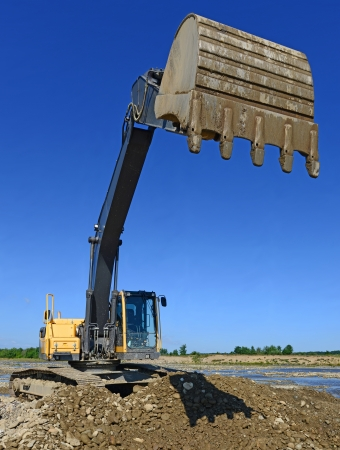 earthwork: Excavator on the work to strengthen the shoreline of the river