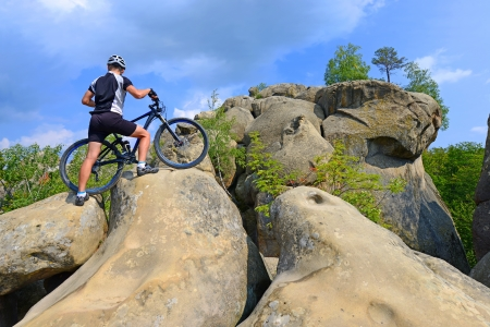 The man with the bike on the steep cliffs  photo