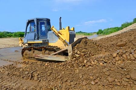 cours d eau: Le bulldozer effectue des travaux dans le lit de mar�e de la rivi�re de montagne petit