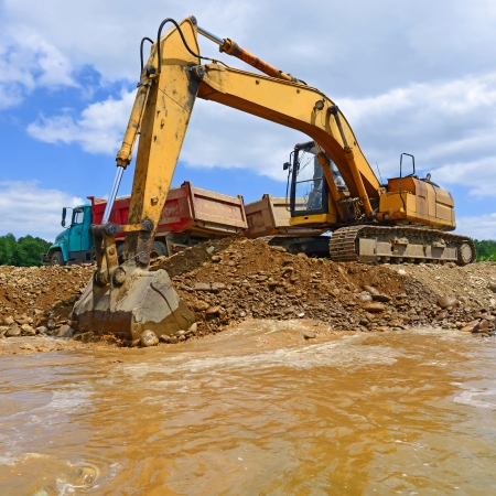 Extracting and loading gravel excavated in the mainstream of the river photo