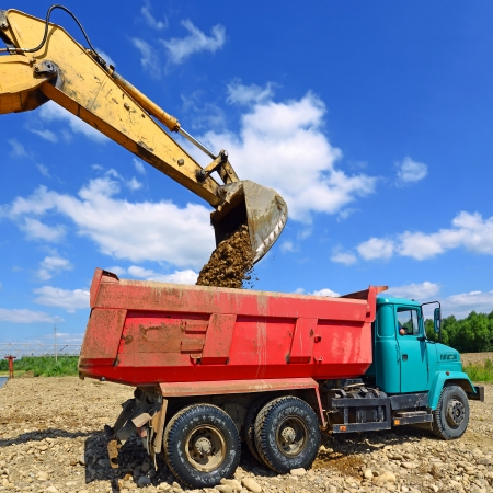 loads: Excavator loads gravel car Stock Photo