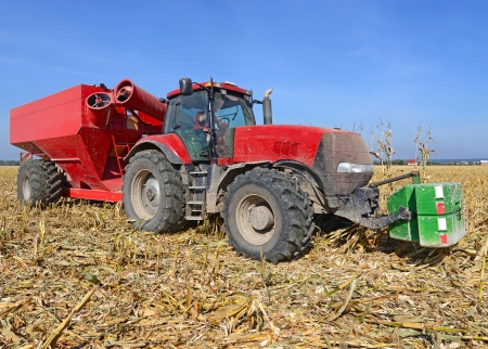 tenure: A tractor with a trailer to transport the grain to harvest corn  Stock Photo