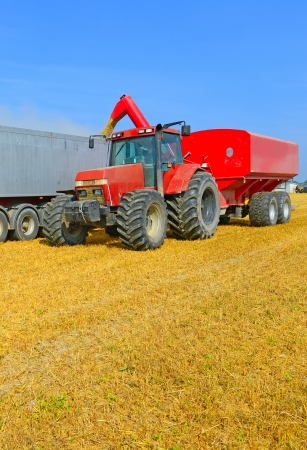 farm implement: Overloading grain silo with a tractor in a car
