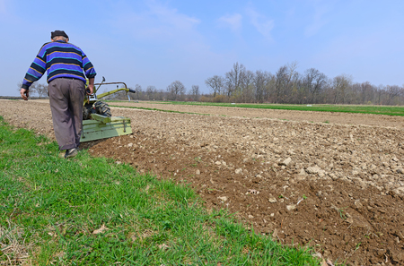The farmer processes a spring field the motor-block photo