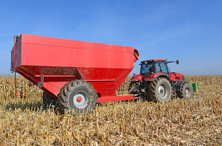 agricultural application tractor: A tractor with a trailer to transport the grain to harvest corn  Stock Photo