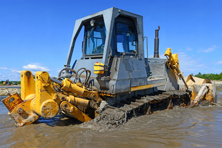 earthwork: The bulldozer performs works in the tideway of mountain small river