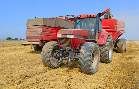 tanker type: Overloading grain harvester into the grain tank of the tractor trailer