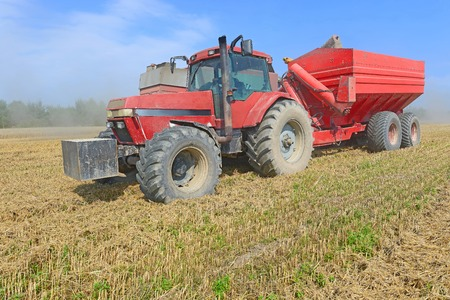 Overloading grain harvester into the grain tank of the tractor trailer photo