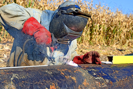 Welder on the pipeline repairs photo