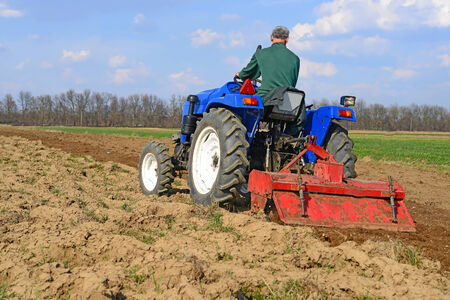 agricultural tenure: Farmer on tractor handles field