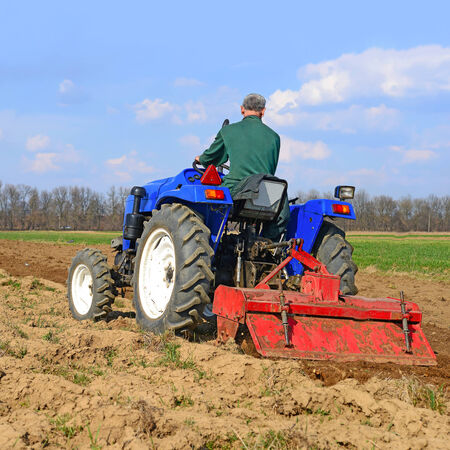 tenure: Farmer on tractor handles field
