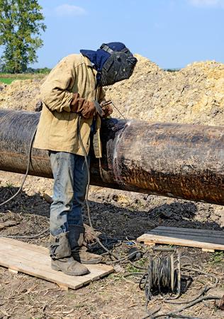Welder on the pipeline repairs photo