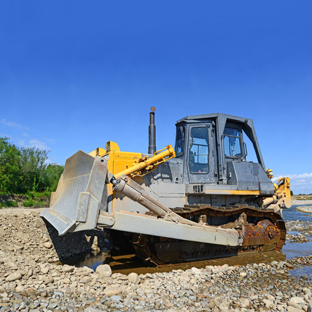 fabricating: The bulldozer performs works in the tideway of mountain small river