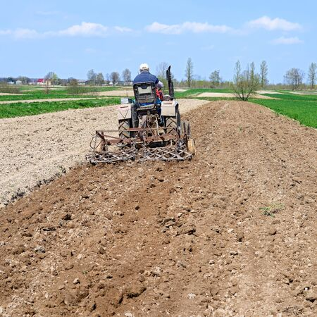 agricultural application tractor: Farmer on tractor handles field