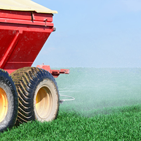 agricultural application tractor: Adding fertilizer in the grain field Stock Photo