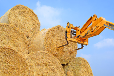 Telescopic handler for storing bales of straw on the ground storage