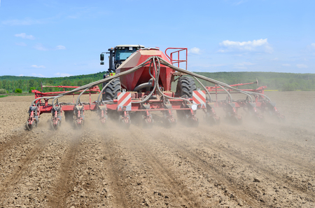 hauling tractor: Planting corn trailed planter in the field