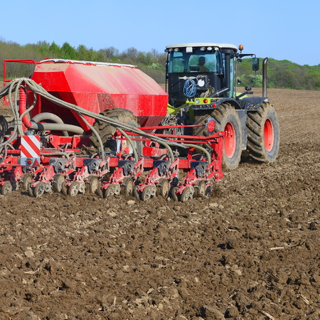 hauling tractor: Planting corn trailed planter in