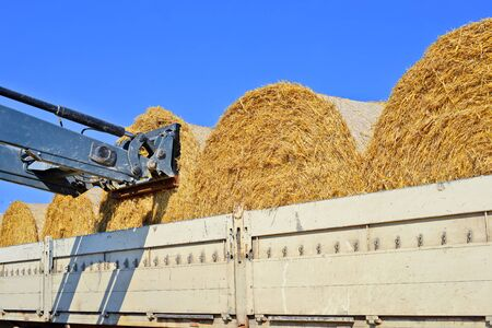 equipping: Loading bales of straw on the car
