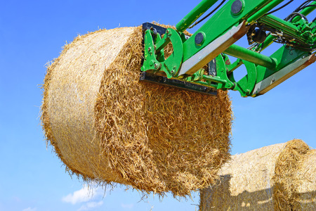 Moving bales of straw tractor with machining attachments