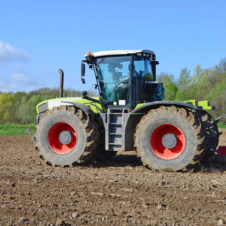 Modern tractor on field works