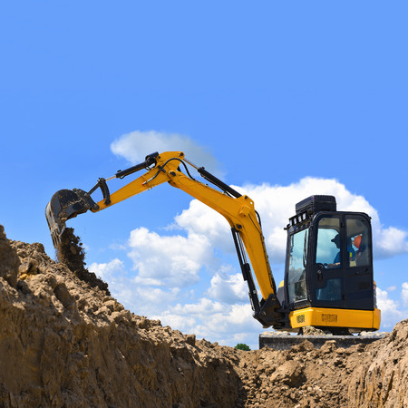 The modern excavator  performs excavation work on the construction site Archivio Fotografico