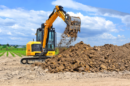 The modern excavator  performs excavation work on the construction site 스톡 콘텐츠