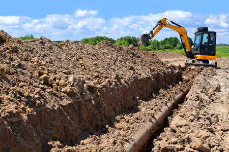 The modern excavator  performs excavation work on the construction site 写真素材