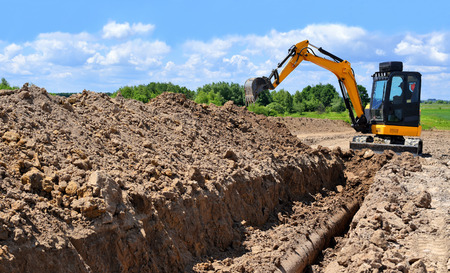 A modern excavator is performing excavation work on the pipeline repair Banco de Imagens - 83930145