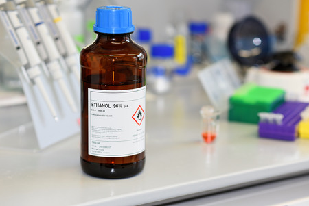 Ethanol in the jar on the working surface in the laboratory. Foto de archivo