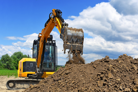 construction project: The modern excavator  performs excavation work on the construction site Stock Photo