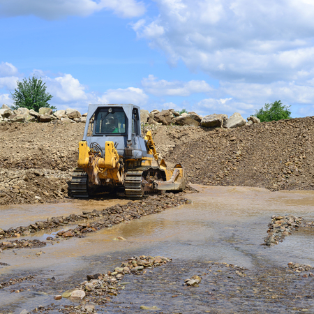 The bulldozer performs works in the tideway of mountain small river