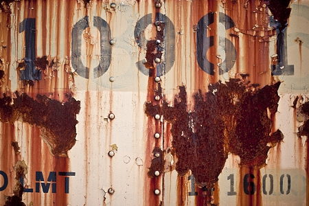 corroded: Interesting and unique capture of a vintage metallic sign which includes decorative looking streaks of rust and alpha-numeric characters