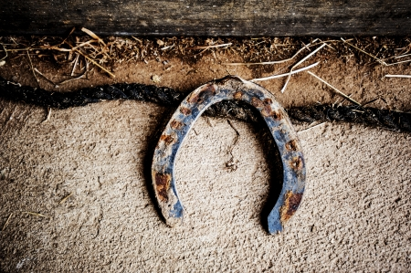 silver horseshoe: An antique nostalgic looking horseshoe on a barn floor, with rope, dust, and hay.  Perfect for any Western or agricultural theme.