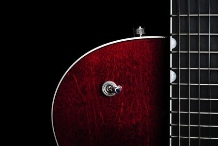 Shiny and sleek red electric guitar again a black back drop photo