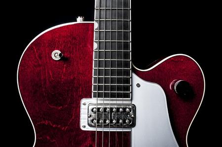 sleek: Shiny and sleek red electric guitar again a black back drop