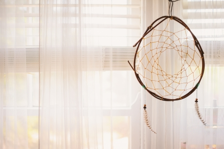 atrapasueños: Disfrute de esta imagen atmosférica de un dreamcatcher del nativo americano, suspendido en frente de una ventana hermosa mañana