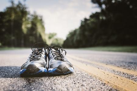 Lone paar nieuwe loopschoenen, gewoon wachten om gebruikt te worden op een open weg Stockfoto