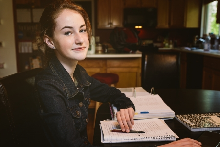 teenaged: Teenaged girl is studying at the family kitchen table