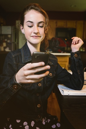 teenaged: Teenaged girl is studying at the family kitchen table and researches something on her phone