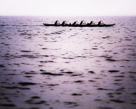 Womens kayaking team practices in at dusk in Kailua Kona Hawaii photo