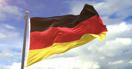 German Flag On Sky Background. Wave And Fabric German Flag. Фото со стока